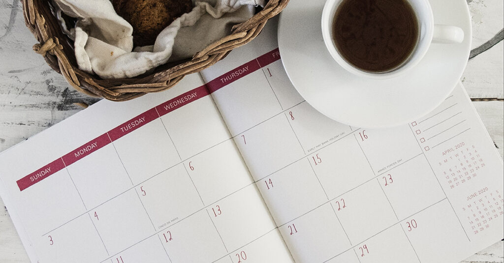 Photo of a calendar, a basket with muffins, and a cup of coffee or tea