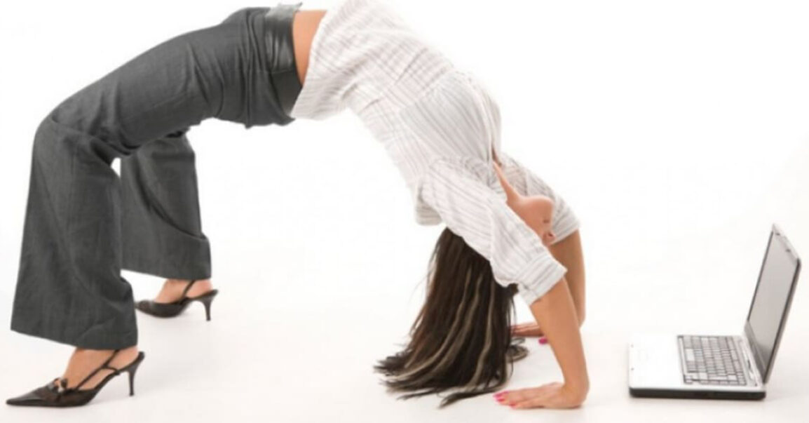 woman in business clothes doing a backbend in front of a laptop