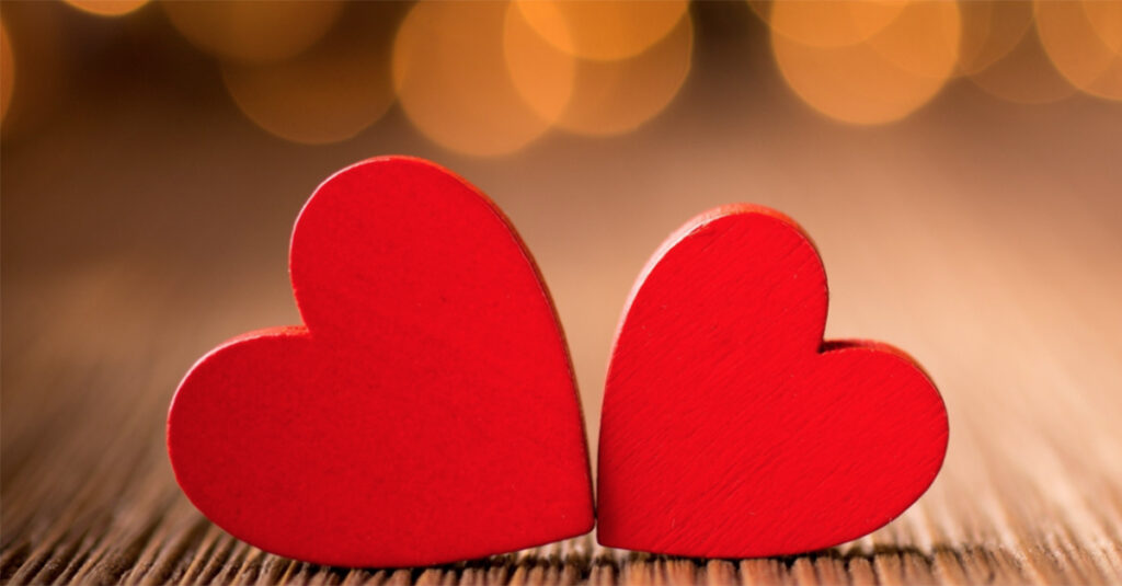 Photo of two red wooden hearts, one slightly larger than the other, lying on their sides with the points at the bottom touching